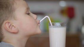 Jongen die een smakelijke drank thuis drinken door een stro stock videobeelden