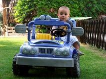 Jongen die een stuk speelgoed auto drijft Royalty-vrije Stock Foto's