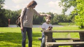 Jongen die een tablet in een park spelen stock video