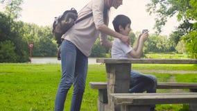 Jongen die een tablet in een park spelen stock videobeelden