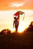 Jongen die een vlieger dragen tegen een dramatische zonsondergang Stock Afbeeldingen
