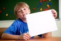 Jongen die een wit blad van document steunt Stock Foto