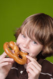 Jongen die een zachte pretzel eet Stock Foto