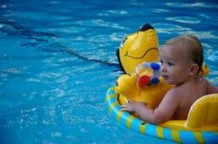 Jongen die in een zwembad drijft Stock Foto