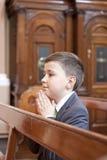 Jongen die en in de kerk knielt bidt. stock afbeeldingen