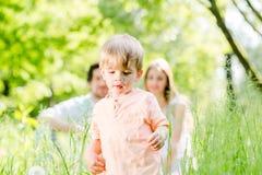 Jongen die en op weide met de familie lopen spelen stock afbeelding
