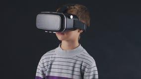 Jongen die ervaring in het gebruiken van VR-Hoofdtelefoon krijgen Vergroot werkelijkheidsapparaat die tot virtuele ruimte voor sm stock videobeelden