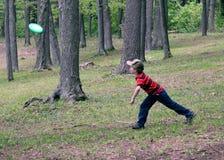 Jongen die Frisbee speelt stock fotografie