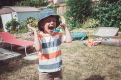 jongen die gestripte t-shirt en hoed met grappige gezichtsuitdrukking buiten dragen op huisbinnenplaats op de zomerdag, het schre stock foto