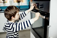 Jongen die gevaarlijk met de knoppen op de oven spelen Stock Afbeelding