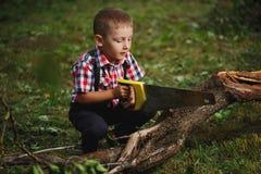 Jongen die gevallen boom in tuin zagen stock afbeeldingen