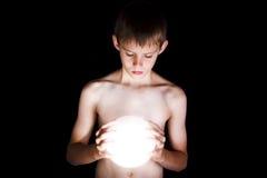Jongen die gloeiende kristallen bol onderzoekt Royalty-vrije Stock Afbeelding