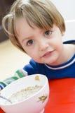 Jongen die Graangewas met Melk eten Stock Foto