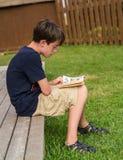 Jongen die grappige boeken lezen Stock Foto's