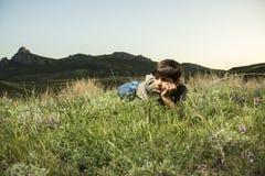 Jongen die in gras bij achtergrond van de bergen liggen Royalty-vrije Stock Afbeelding