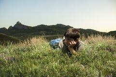 Jongen die in gras bij achtergrond van de bergen liggen Stock Afbeelding