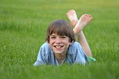 Jongen die in Gras legt Stock Fotografie