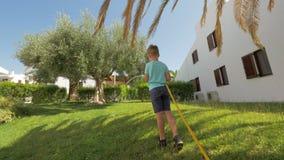 Jongen die groen gazon water geven dichtbij het huis stock videobeelden