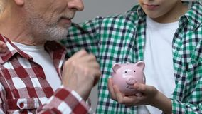 Jongen die grootvader, oude mens koesteren die muntstukken in spaarvarken, besparingenconcept zetten stock videobeelden