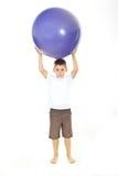 Jongen die grote bal op hoofd houdt Royalty-vrije Stock Afbeeldingen