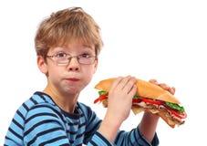 Jongen die grote sandwich op wit eten stock foto's