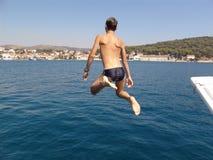 Jongen die in het overzees springt Stock Foto's