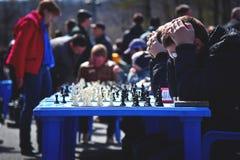 Jongen die in het spelen schaak op de straat denken Royalty-vrije Stock Afbeeldingen