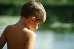 Jongen die in het water staart Stock Afbeelding