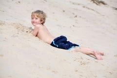 Jongen die in het zand bij de basis van een zandduin legt Royalty-vrije Stock Afbeeldingen