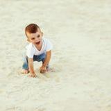 Jongen die in het zand lachen royalty-vrije stock fotografie