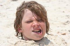 Jongen die in het zand wordt begraven royalty-vrije stock foto's