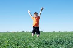 Jongen die hoog, groen gras en blauwe hemel op de achtergrond, het succes, het fortuin, de voltooiing en het winnen springen royalty-vrije stock foto's
