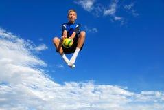 Jongen die hoog met bal springt stock foto