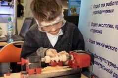 Jongen die houtbewerkingsmachine bestuderen Stock Foto
