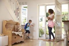 Jongen die Huis voor School met Moeder verlaten Stock Afbeeldingen
