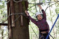 Jongen die in kabelpark beklimmen stock afbeeldingen