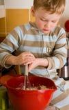 Jongen die kok helpt Royalty-vrije Stock Afbeeldingen