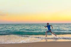 Jongen die langs het strand bij zonsondergang lopen royalty-vrije stock foto