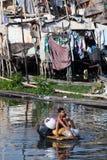 Jongen die langs Paranaque Rivier Filippijnen paddelt stock fotografie