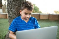 Jongen die laptop met behulp van bij park royalty-vrije stock afbeelding