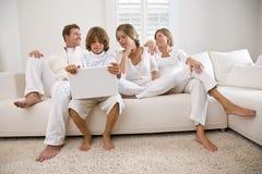 Jongen die laptop zitting met familie op witte bank gebruikt Stock Foto's