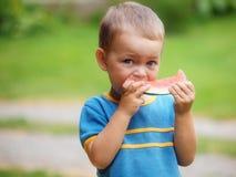 Jongen die meloen eet Stock Fotografie