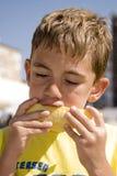 Jongen die meloen eet Stock Foto