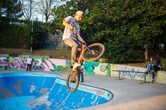 Jongen die met BMX-fiets op een BMX-zitting in de stad springen stock afbeeldingen
