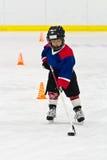 Jongen die met de puck bij ijshockeypraktijk schaatsen Royalty-vrije Stock Afbeelding