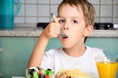 Jongen die met een vork bij de lijst eten Stock Fotografie