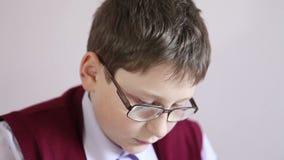 Jongen die met glazen de tablet spelen op school stock videobeelden