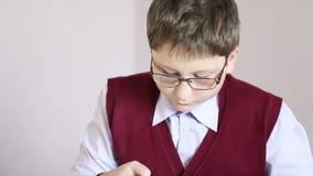 Jongen die met glazen de tablet spelen op school stock video