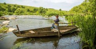 Jongen die met hengel in een houten boot vissen Stock Foto