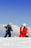 Jongen die met moeder in de winterpark wordt gespeeld stock fotografie